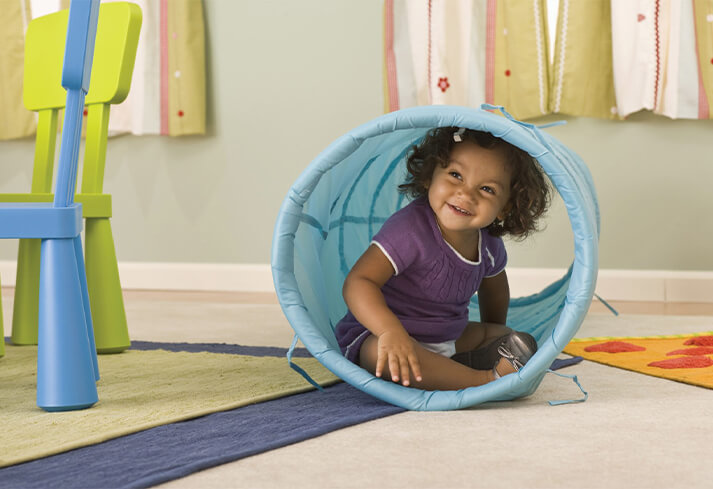 Child playing in a toy tube.
