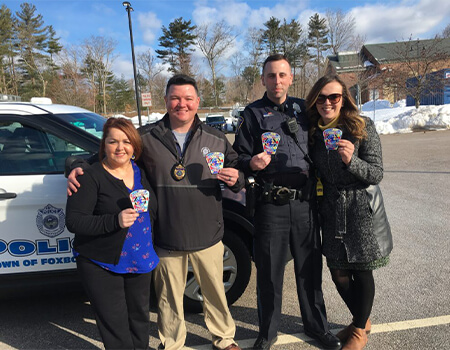 Police Officer's and citizens standing in front of a police car holding up autism patches.