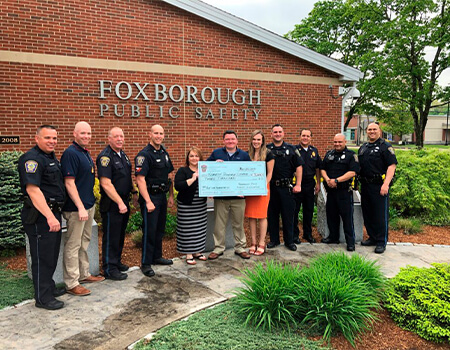 Police officers and citizens holding up a giant check in front of the police department building.