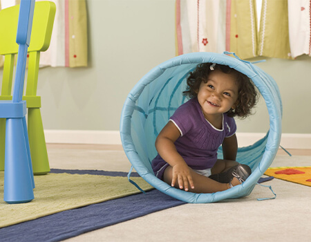 Infant playing in a toy tube.